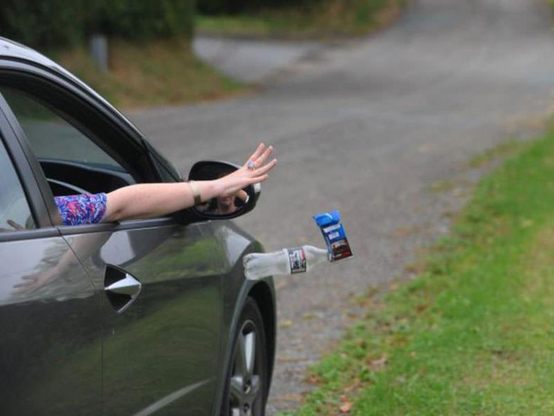 ریختن بطری خالی آب و آشغال شکلات از ماشین توسط یک خانم