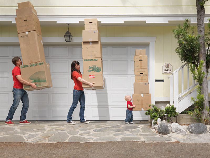 پدر و مادر و بچه در حال حمل کردن کارتنهای اسباب کشی