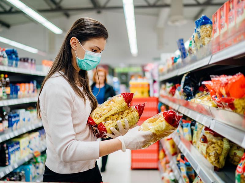 خانمی با دستکش و ماسک در حال خرید در دوران ویروس کرونا