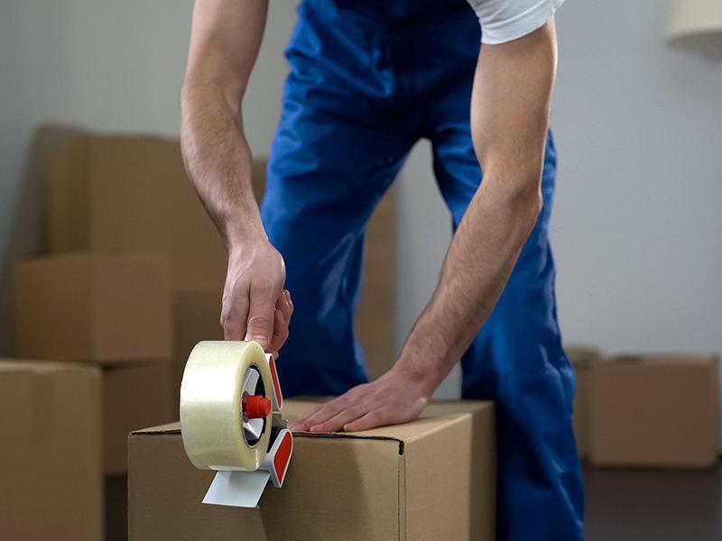 کارگر بستهبند در حال چسب زدن به کارتن