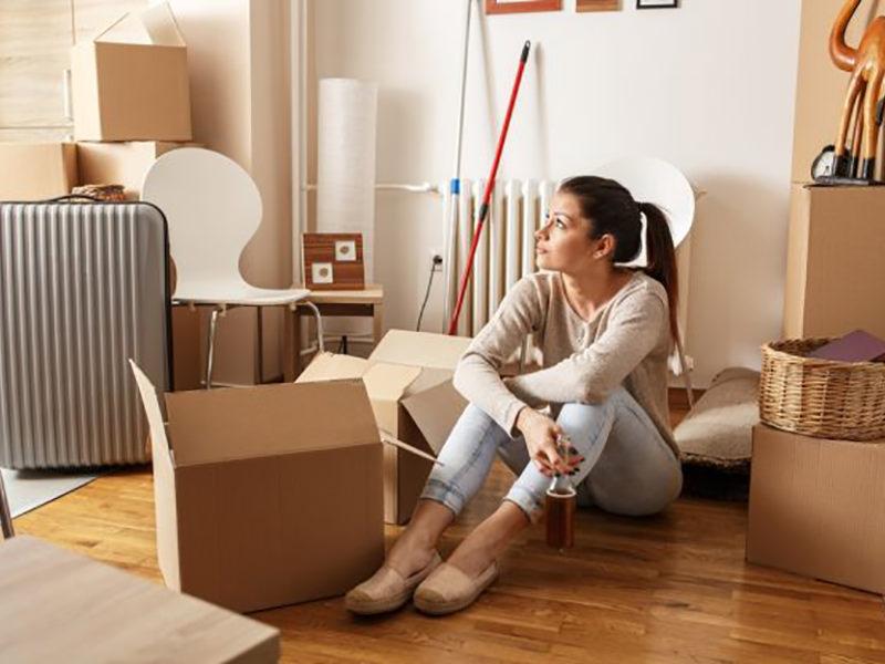 خانمی در حال بسته بندی وسایل خانه