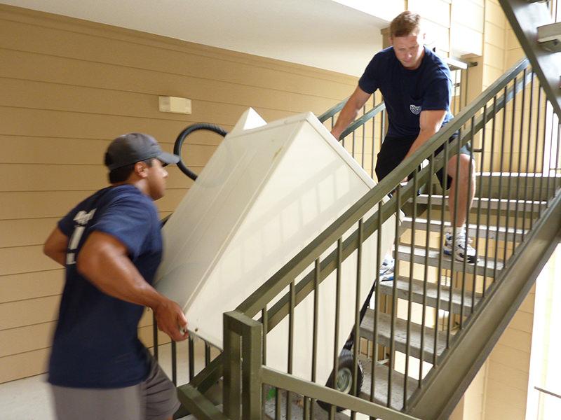 تیم باربری در حال بالا بردن ماشین لباسشویی